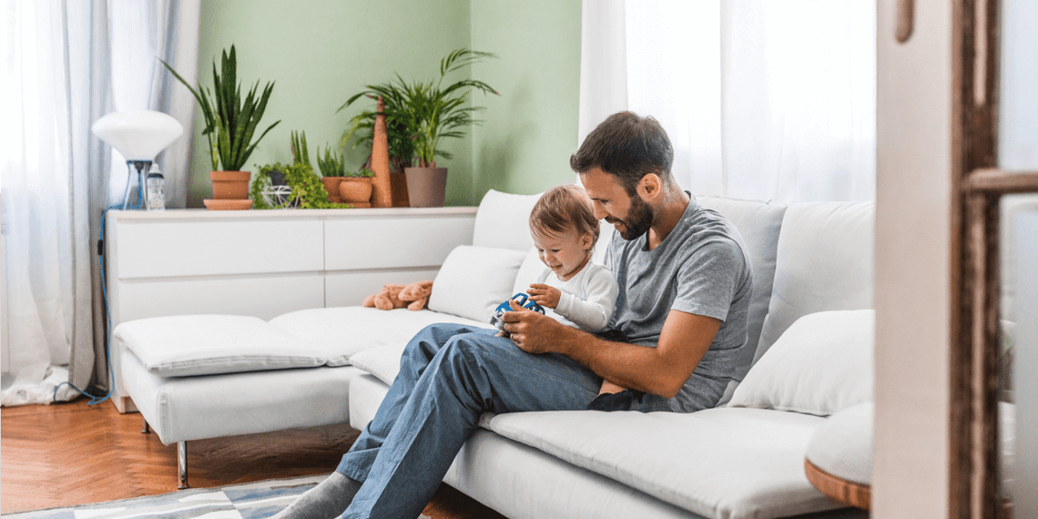 man and young child playing in living room