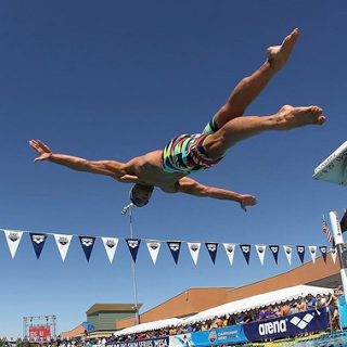 An Olympic swimmer dives into the pool