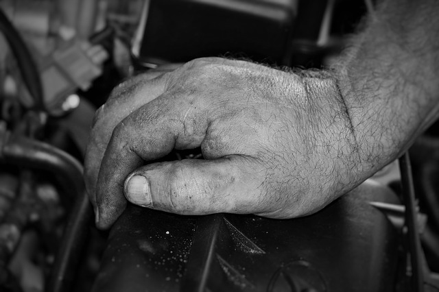 A mans hand resting on an engine.