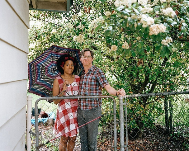couple standing behind fence