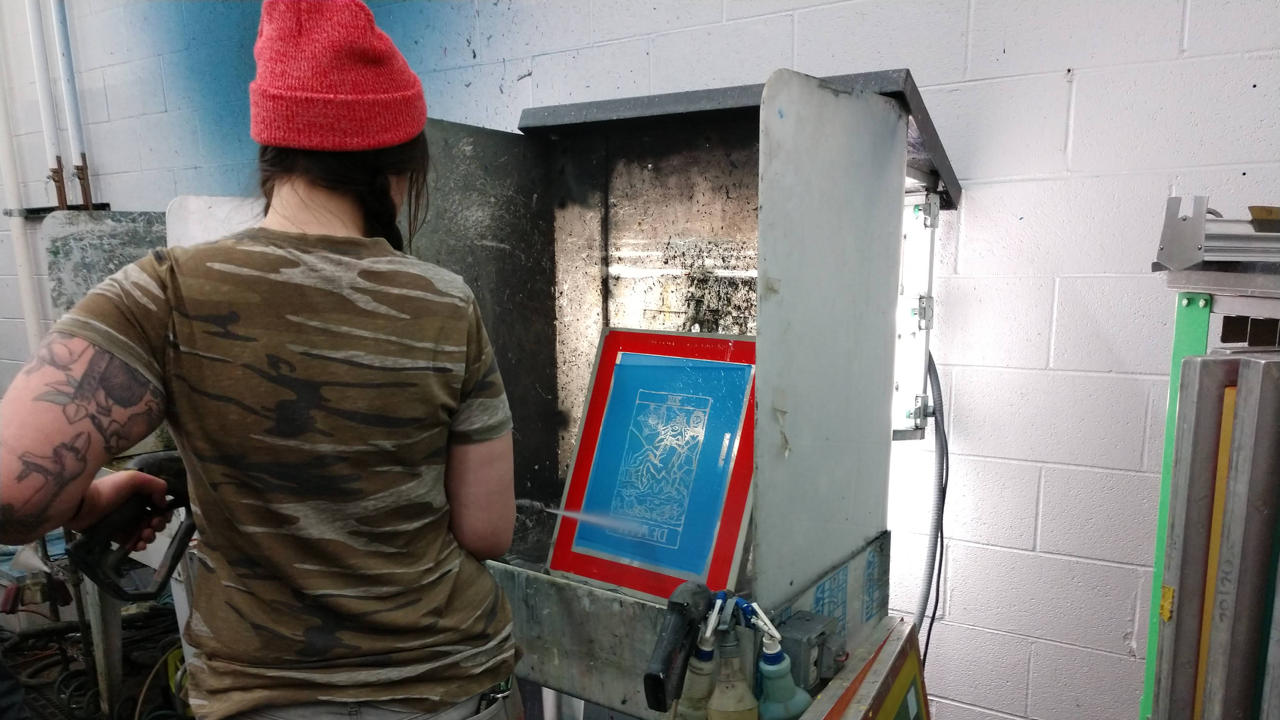A woman cleans a screen used for screen printing at Barrel Maker Printing