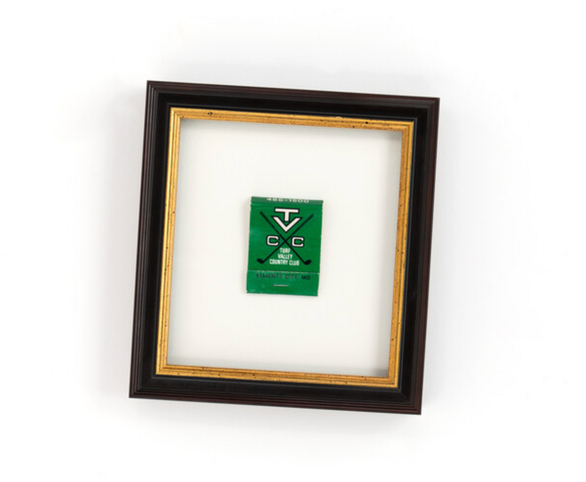 Green matchbook float mounted in black and gold frame