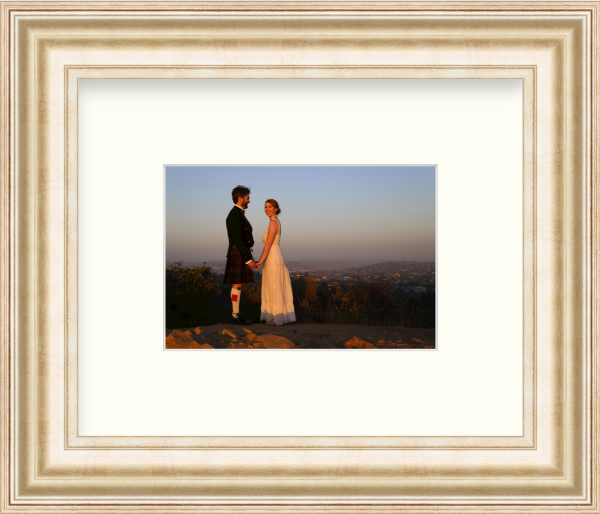 Wedding photo of couple in landscape in gold frame