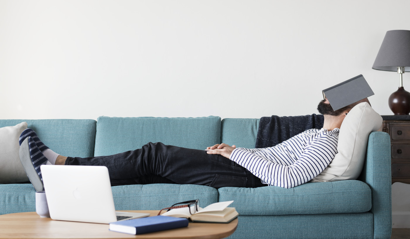 man laying on couch sleeping with book over head
