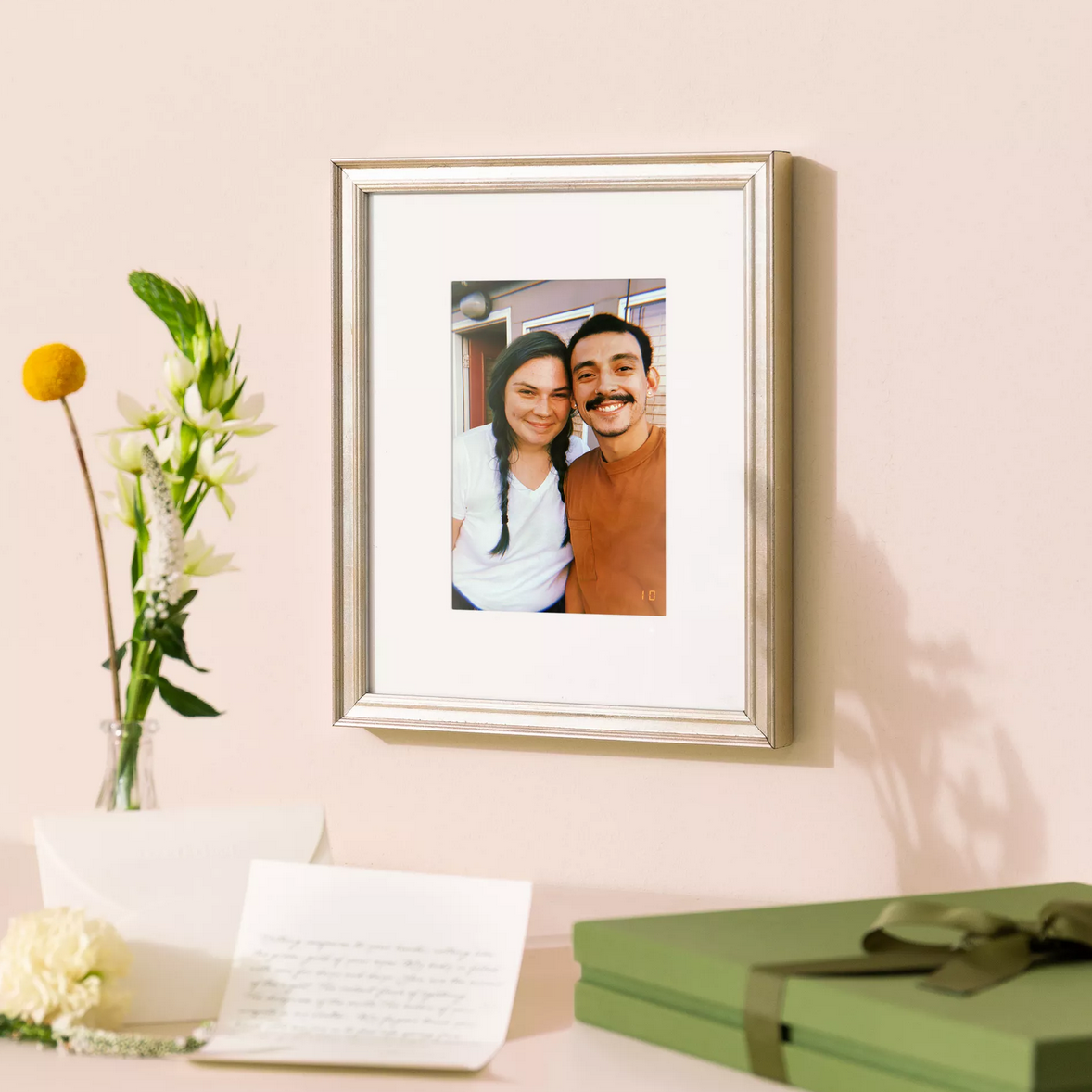 silver frame with white mat and photo of two friends