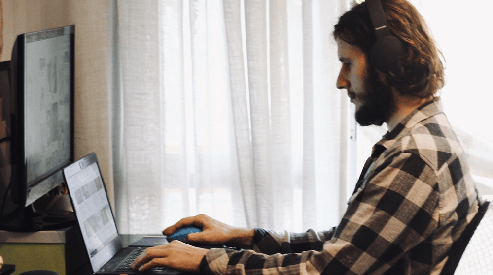Man working on laptop with headphones on