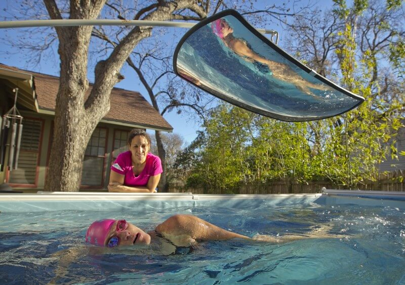 Kim Brackin coaches a swimmer in her backyard Endless Pool