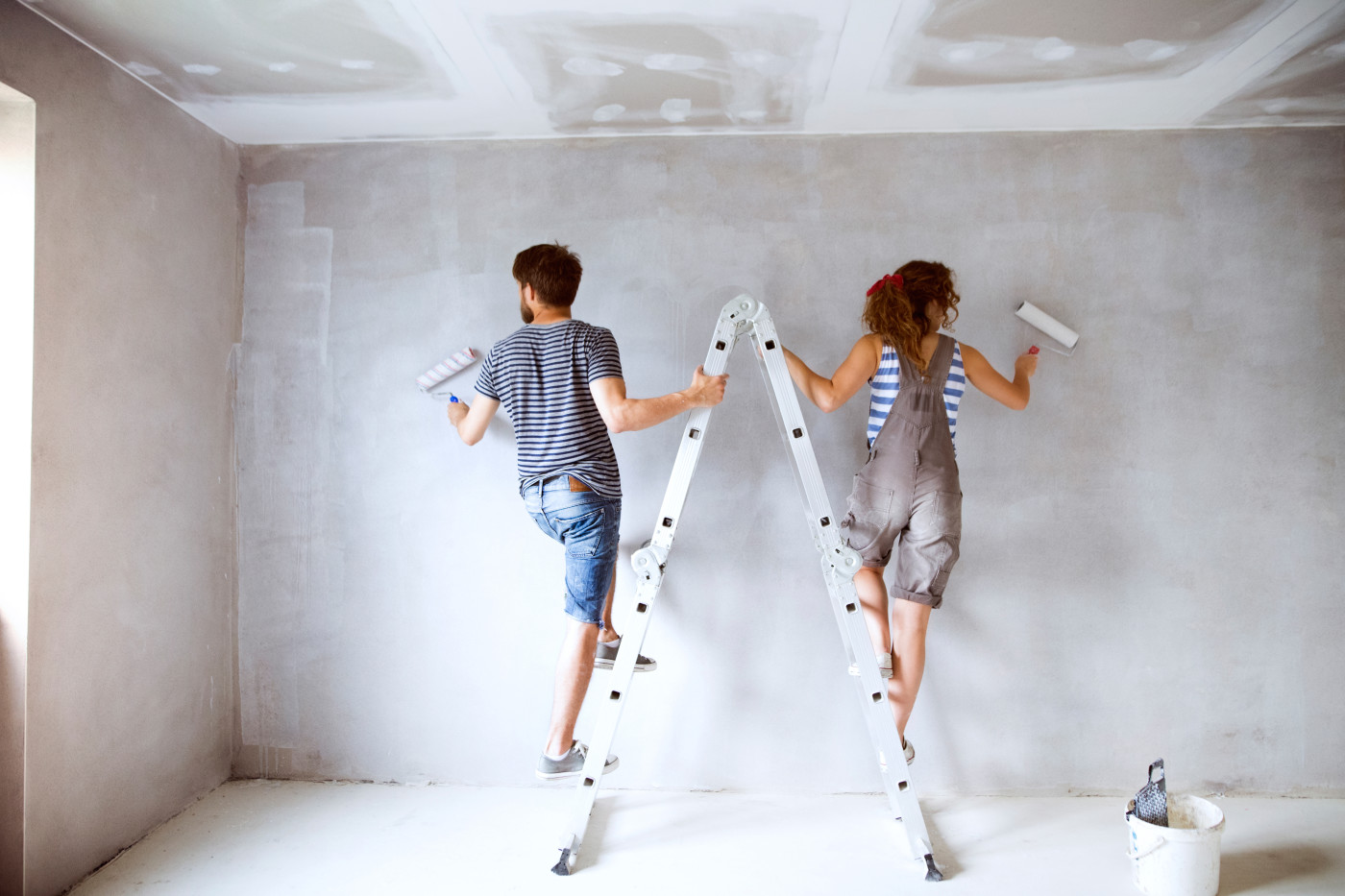 couple standing on ladder painting wall