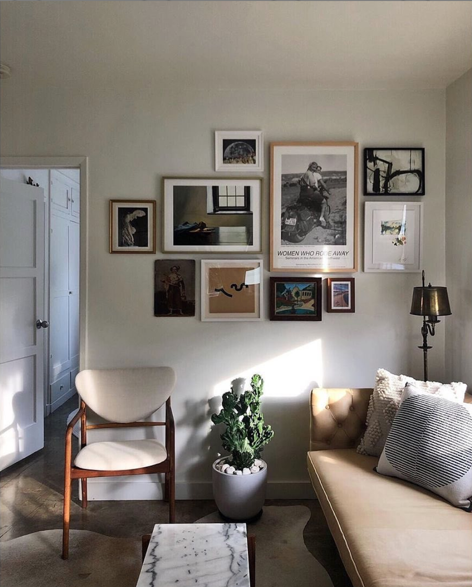 gallery wall of framed pictures on wall in living room