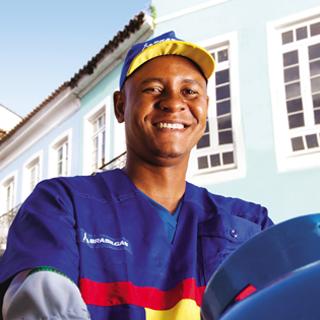 Foto de um homem negro, funcionário da Ultragaz sorrindo, vestindo uniforme nas cores azul, amarela e vermelha com logo estampado no peito do lado esquerdo. Ao fundo um céu azul e uma casa azul mais clara.