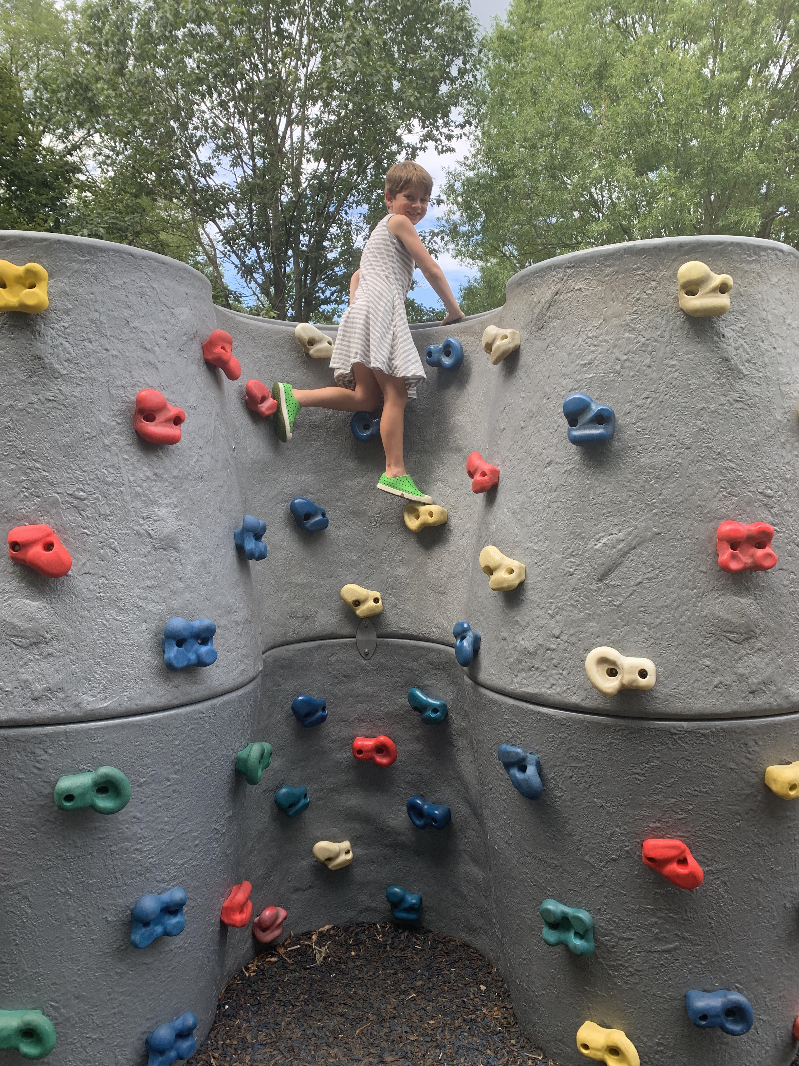 6 year old boy in a gray striped sleeveless dress from Primary rock climbing
