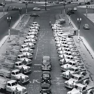 Foto em preto e branco tirada em 1950 vista de cima de um pátio com 32 caminhões da Ultragaz estacionados.