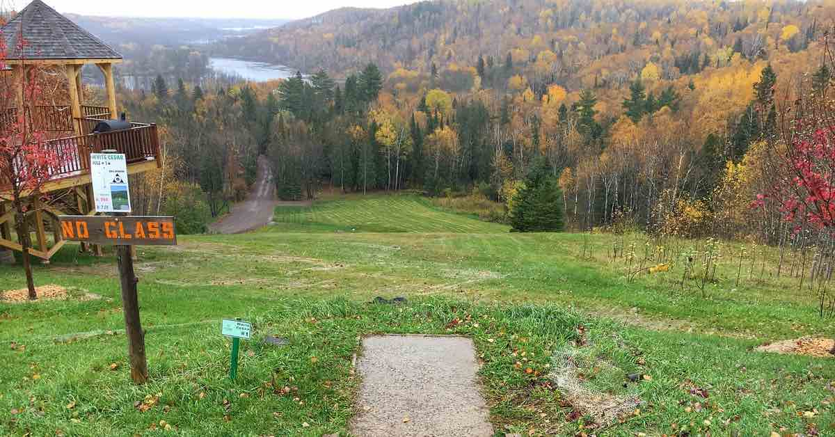 A disc golf tee pad overlooking a valley full of trees in fall colors