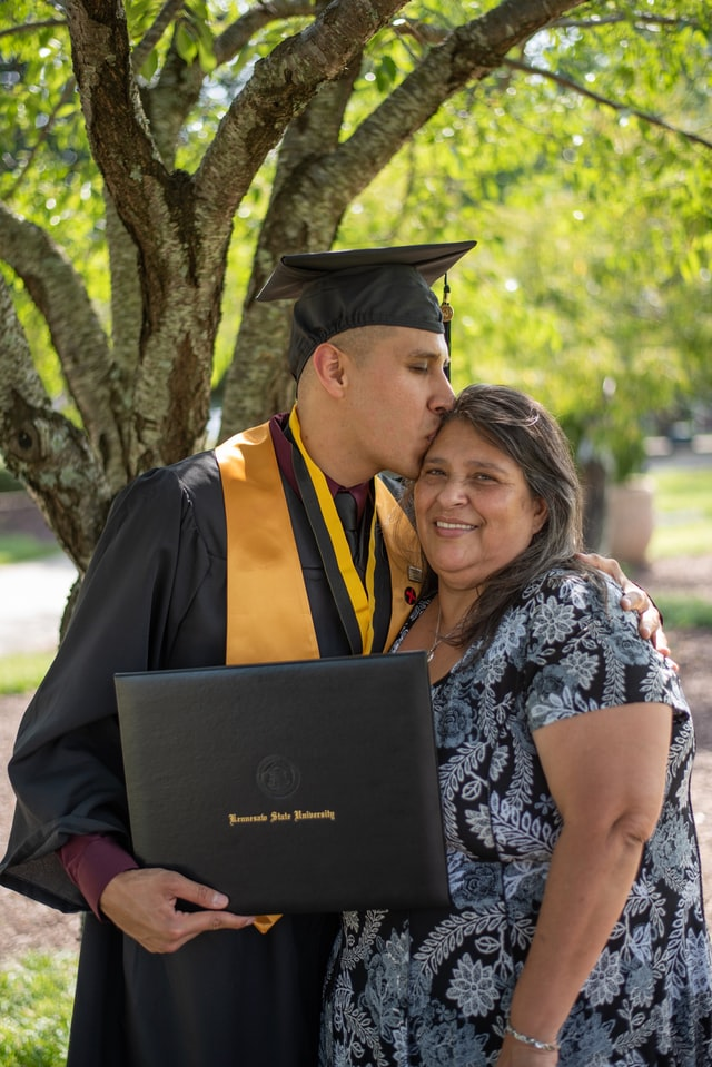 Man in graduation cap holding diploma and kissing woman's head