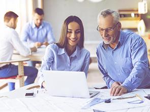Foto de um homem e uma mulher, ambos sorrindo e  vestidos com camisas azuis clara, navegando em um computador. Ao fundo, dois homens também mexendo no computador.