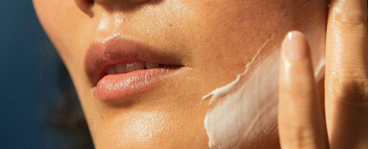 woman spreading cream on chin