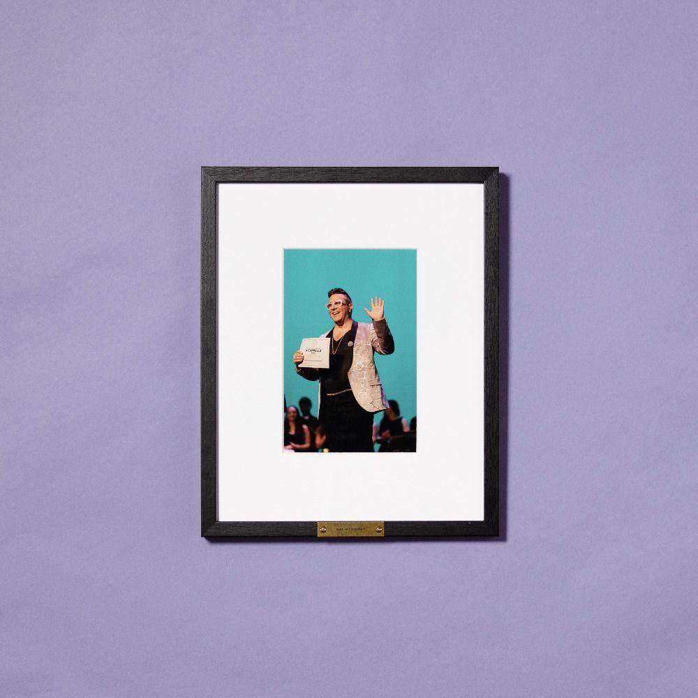 framed photo of man accepting award