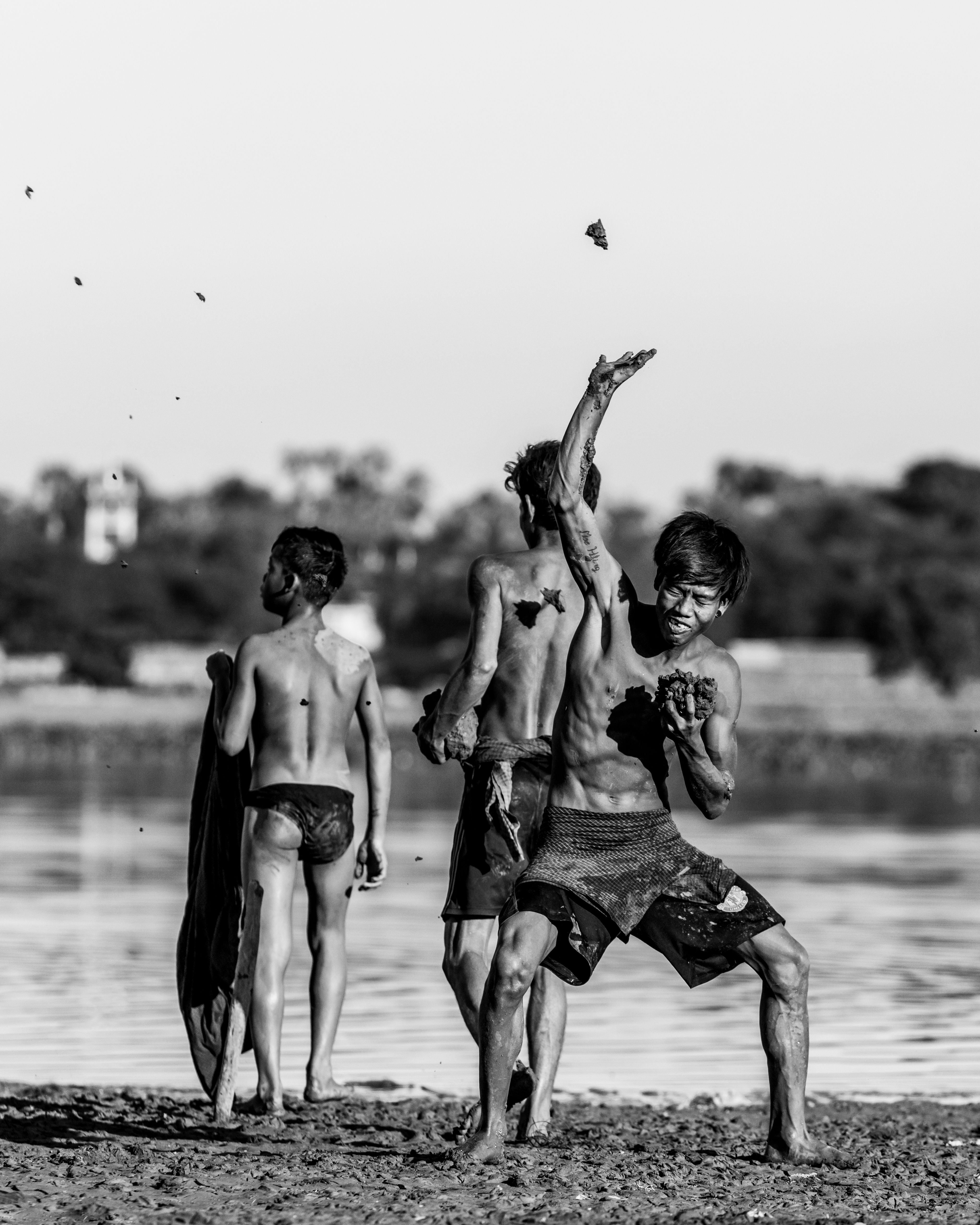 teens playing in mud on the beach