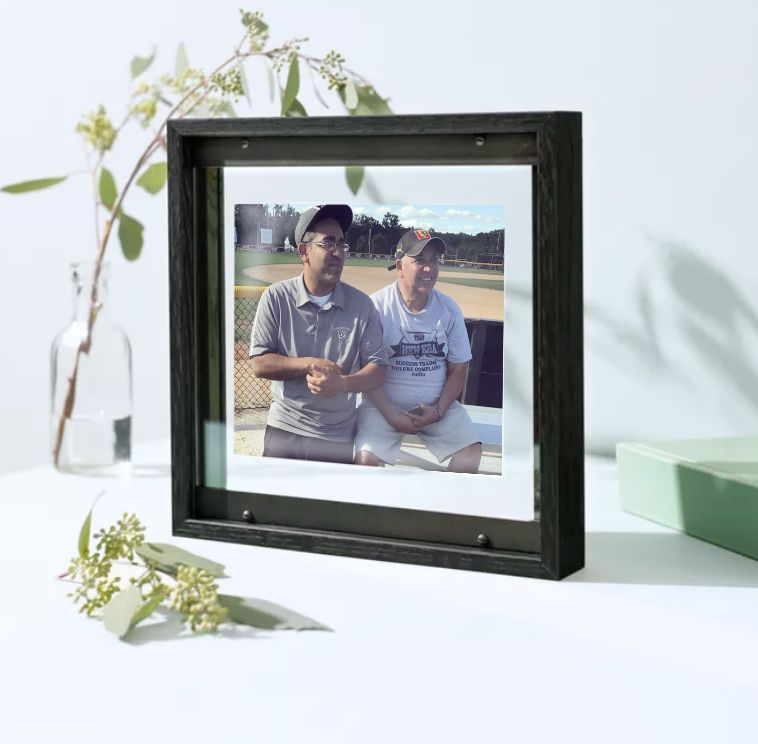 two dads in baseball caps in black frame