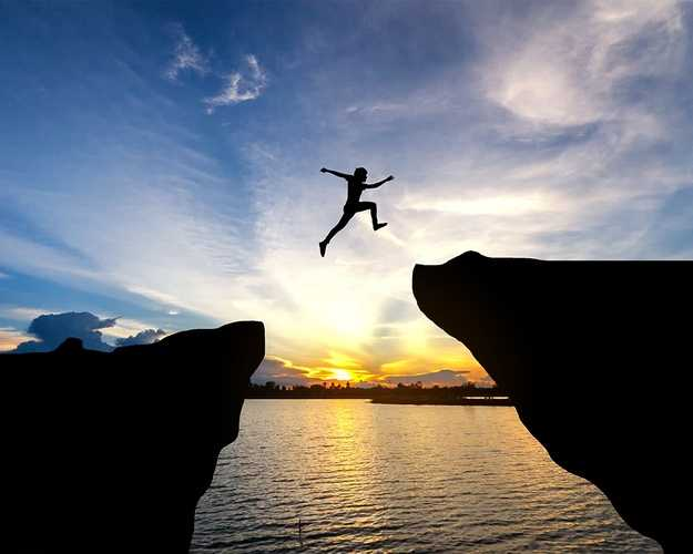 Person jumps over gap formed by two cliffs with the sunsetting over the water in the background
