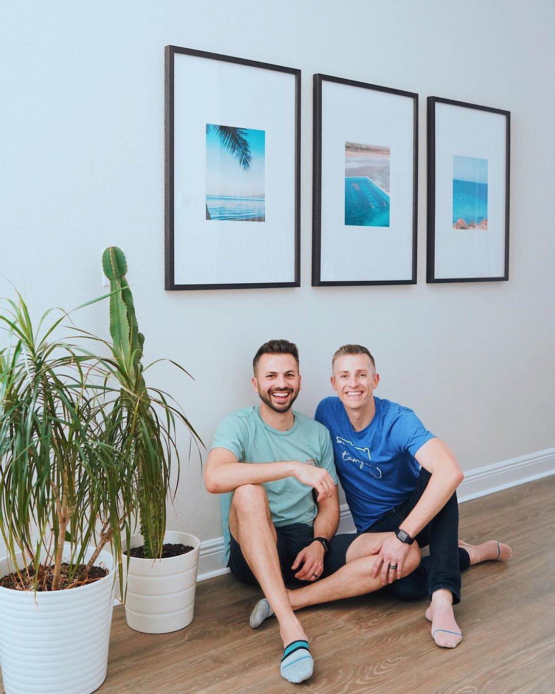 triptych gallery in hallway with two smiling men and a plant