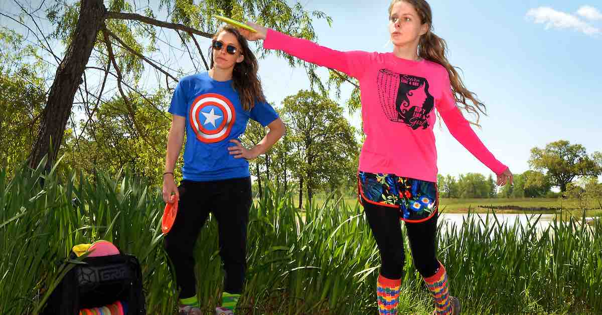 Two young women in colorful outfits playing disc golf on a sunny day