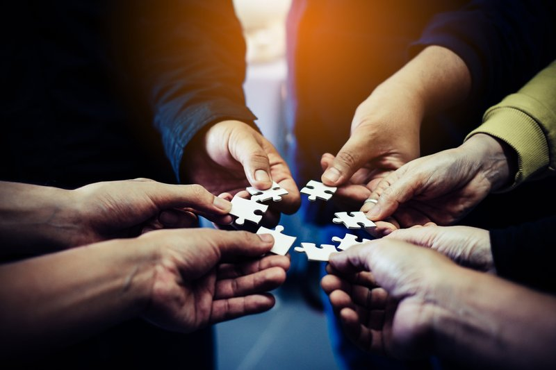 Group of hands holding individual puzzle pieces form a circle