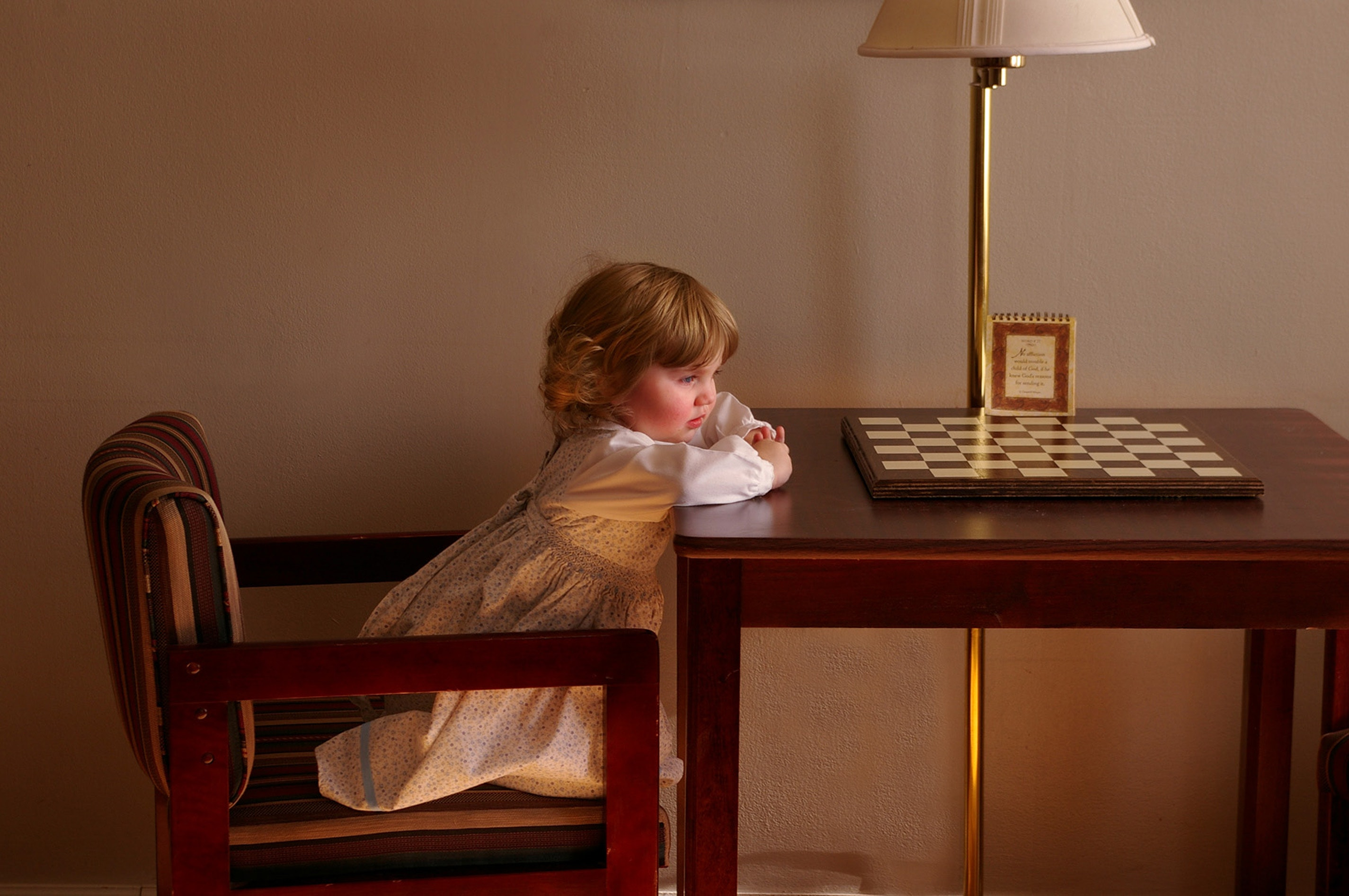 Young girl looking at chess board