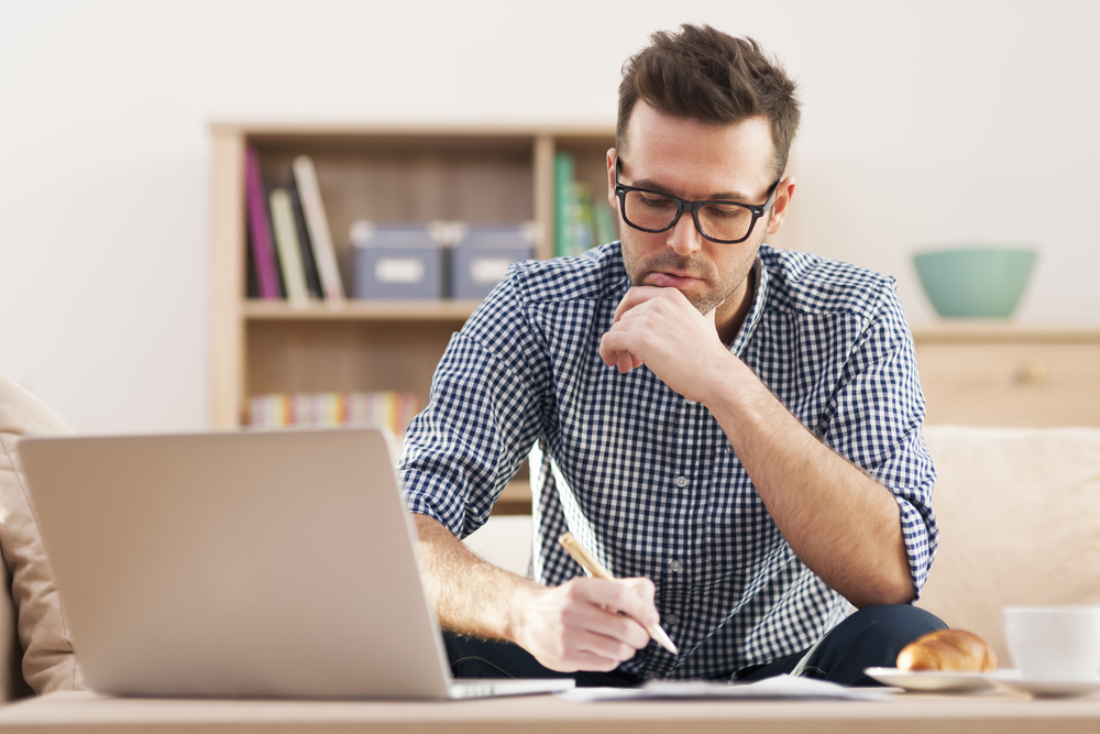 man making notes with laptop open