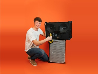 Emil fixing a SOUNDBOKS with a screw driver in front of a SOUNDBOKS in front of an orange background