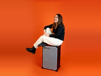 Ewa, in a black outfit sitting on top of a SOUNDBOKS in front of an orange background