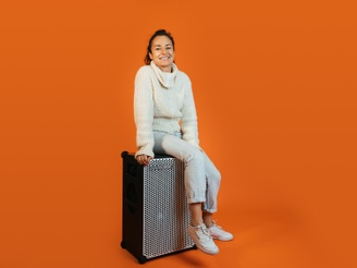 Anjuli, in a white outfit sitting on top of a SOUNDBOKS in front of an orange background