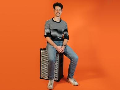 Wouter, digital director at soundboks sitting on a soundboks in front of an orange background
