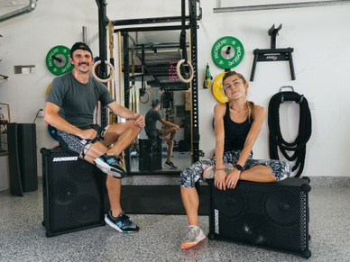 Girl and guy sitting on top of the SOUNDBOKS in a home gym