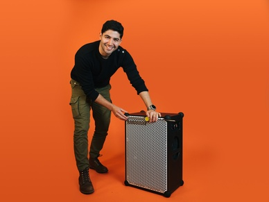 Amir, mechanical engineer measuring a SOUNDBOKS in front of an orange background