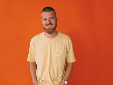 Fred, the creative director at SOUNDBOKS in front of an orange background