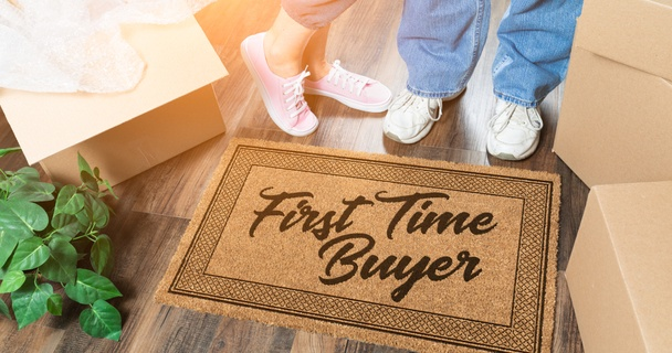 couple standing on first time buyer doormat