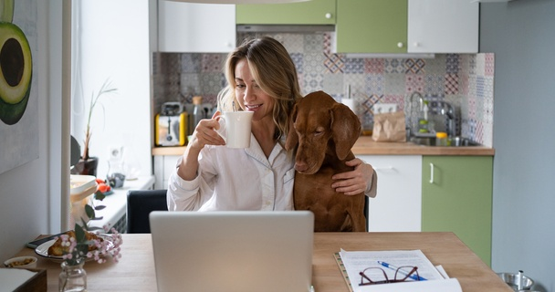 woman having coffee at home on laptop with her dog