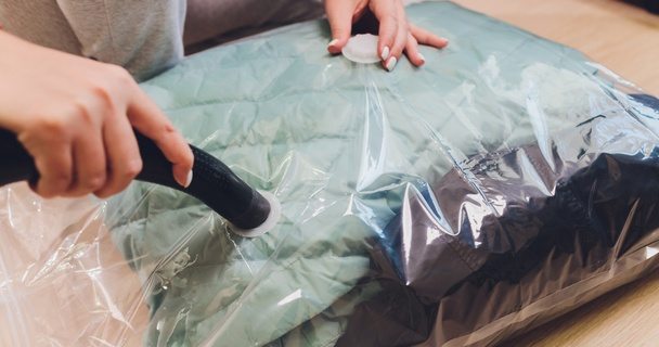 Woman vacuum packing unused clothes for storage