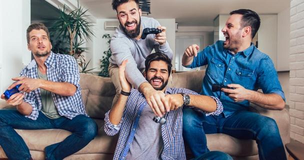 men playing video games on sofa