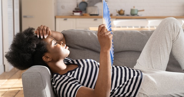 woman cooling down with a fan on sofa at home
