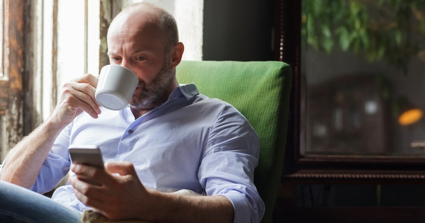man checking phone drinking coffee