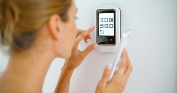 woman using smartphone to control electrical appliances