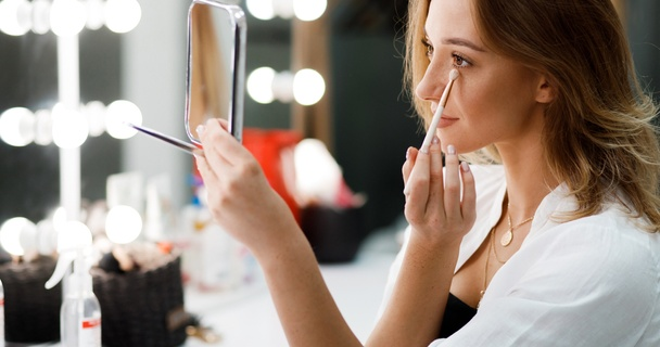 Woman doing her makeup in the mirror