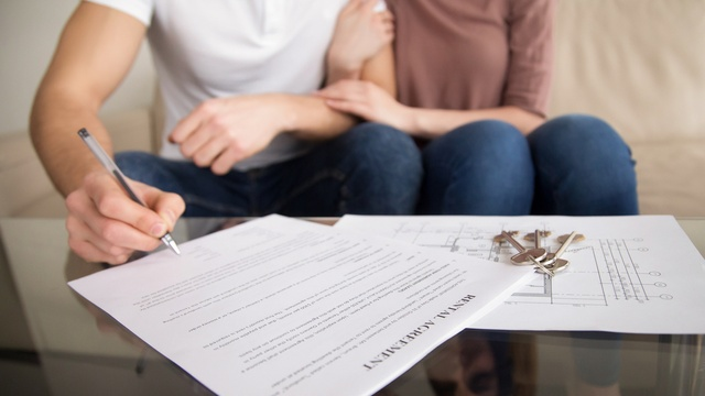 Couple signing tenancy agreement
