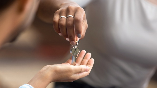 woman handing man keys