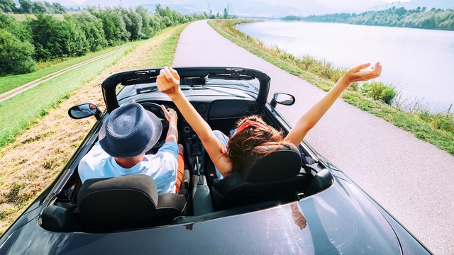 couple driving convertible car on road