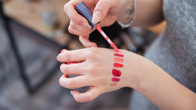 woman testing lip-gloss samples on the back of her hand