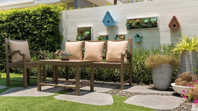 cosy corner of a small garden with painted wall and outdoor furniture