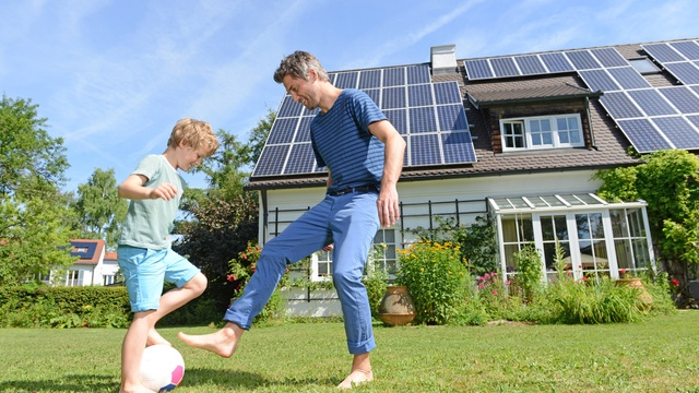 son and father playing in front of solar panel house